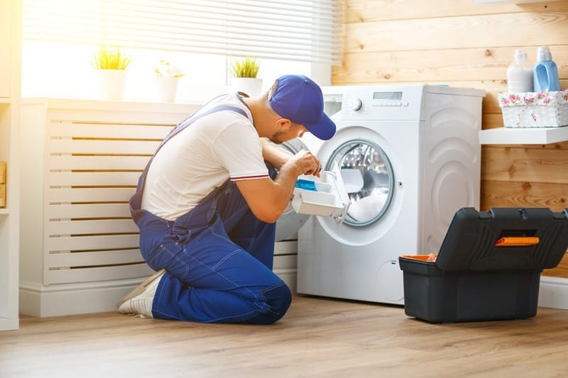 Maintenance man checking a washing machine